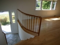 A curved mahogany handrail with curved maple stairs
